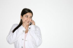 Portrait of Caucasian teen girl whispering into cellphone standing against white background.